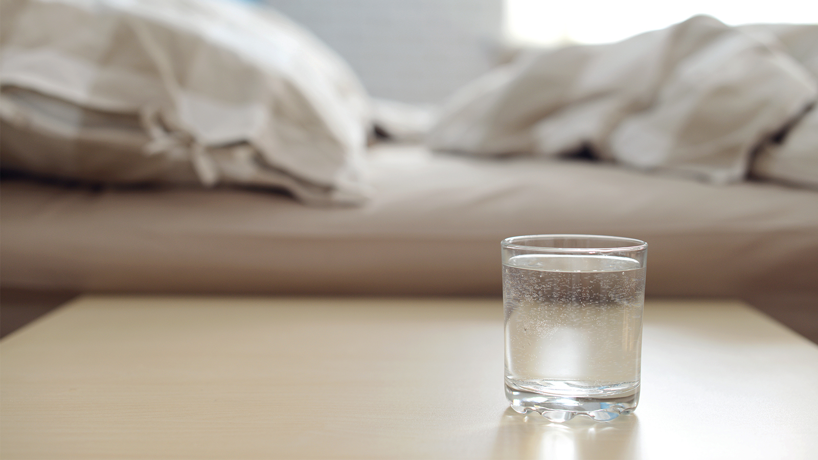 Glas Wasser ans Bett stellen